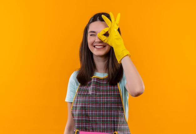 エプロンとゴム手袋の若い美しい女の子は、このサインを通して見てokサインをやって笑っています