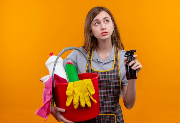Молодая красивая девушка в фартуке держит ведро с чистящими средствами и чистящим спреем, глядя в сторону с грустным выражением лица