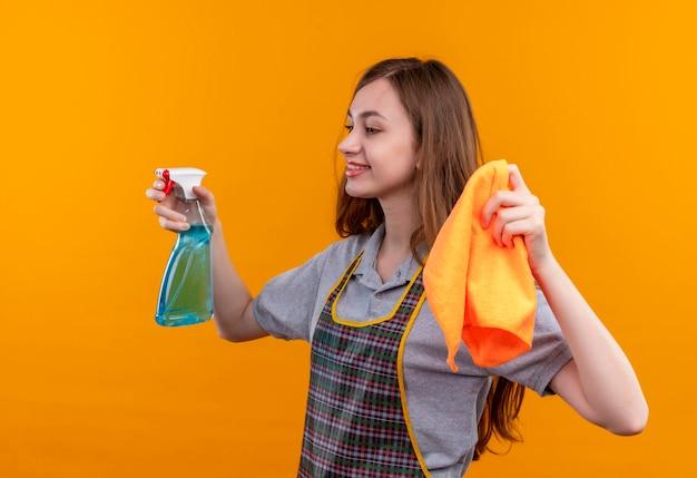 笑顔を脇に見て、掃除の準備ができて、掃除スプレーと敷物を保持しているエプロンの若い美しい少女