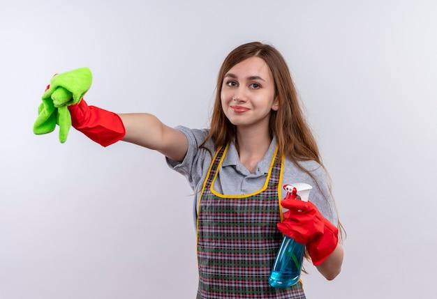 掃除スプレーと敷物を持ってカメラの笑顔を見て、掃除の準備ができてエプロンの若い美しい少女