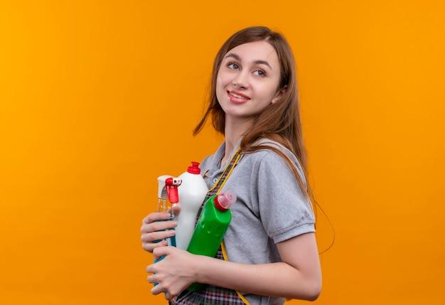 Молодая красивая девушка в фартуке держит чистящие средства, глядя в сторону, улыбаясь дружелюбно, готовая к уборке