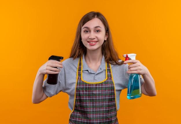 Молодая красивая девушка в фартуке держит чистящие средства, глядя в камеру, улыбаясь дружелюбно, готовая к уборке