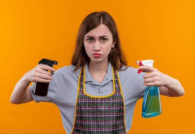 Молодая красивая девушка в фартуке, держащая чистящие средства, смотрит в камеру с серьезным лицом, готовая к уборке
