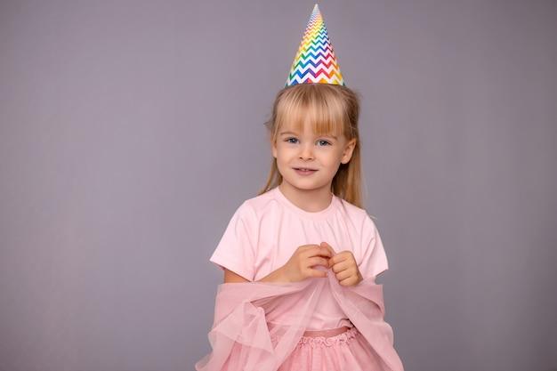 격리 된 배경에 생일 모자에 젊은 아름 다운 소녀