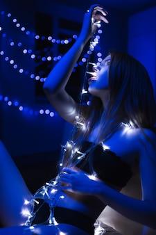 青い部屋で彼女の手に花輪を持つ黒いランジェリーの若い美しい少女
