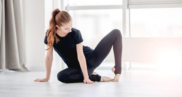 黒の衣装で若い美しい少女はバレエのクラス中に足を伸ばします