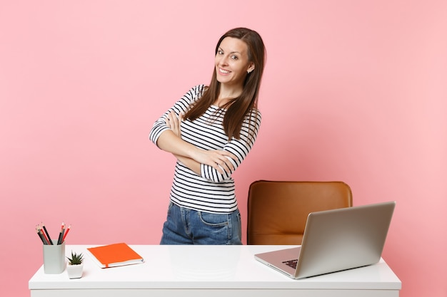パステルピンクの背景に分離された現代的なpcのラップトップと白い机の近くに立って、カジュアルな服を着た若い美しい少女が動作します。業績ビジネスキャリアコンセプト。広告用のスペースをコピーします。