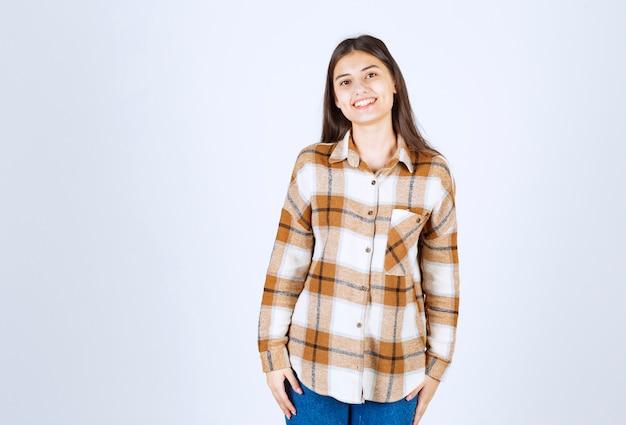 白い壁に立ってポーズをとってカジュアルな服装の若い美しい少女。