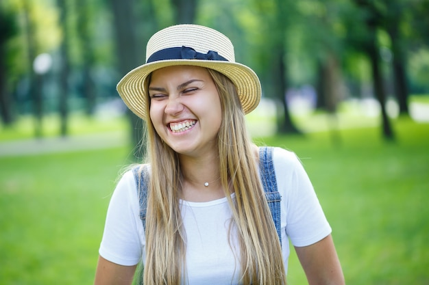 デニムのオーバーオールと公園を歩いている軽い帽子の若い美しい少女