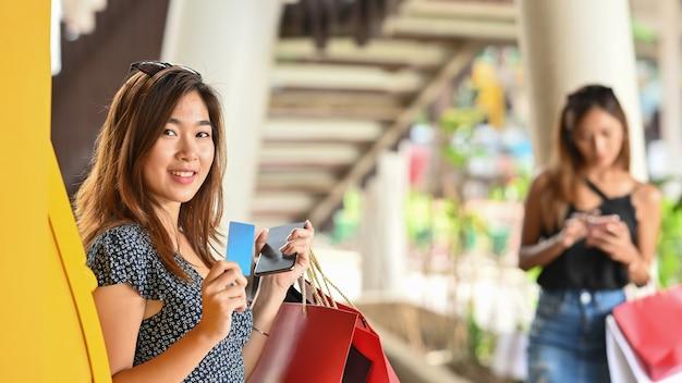 Молодая красивая девушка в платье держит кредитную карточку и хозяйственные сумки в руках, стоя рядом с желтым банкоматом с размытыми женщиной и супермаркетом