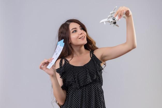 Молодая красивая девушка в платье в горошек, держащая авиабилеты и игрушечный самолетик, весело улыбается, выглядит игриво и счастливо, стоя на белом фоне