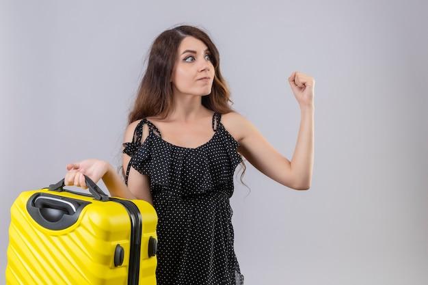 白い背景の上に立っている怒っている顔で脅して拳を上げる旅行スーツケースを保持している水玉のドレスの美しい少女