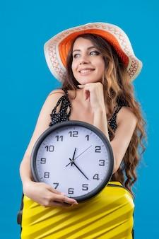 青い背景上の顔に笑顔で待っているスーツケースを持って立っている時計を保持している夏帽子の水玉のドレスの美しい少女
