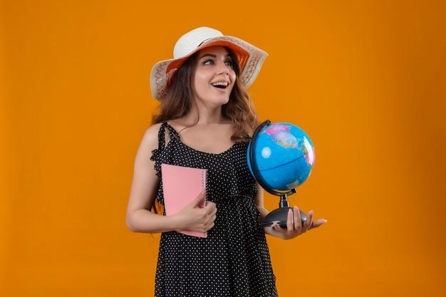 Молодая красивая девушка в платье в горошек в летней шляпе держит глобус и ноутбук, глядя в сторону, улыбаясь со счастливым лицом, стоящим на желтом фоне