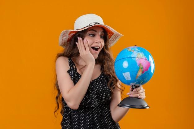 Молодая красивая девушка в платье в горошек в летней шляпе держит глобус, глядя на него изумленно и удивленно, стоя на желтом фоне