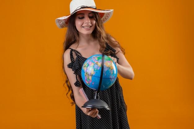 Молодая красивая девушка в платье в горошек в летней шляпе держит глобус, глядя на него, улыбаясь со счастливым лицом, стоящим на желтом фоне
