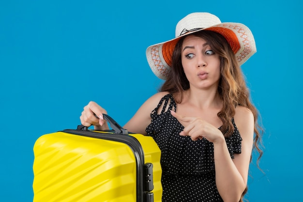Молодая красивая девушка в платье в горошек в летней шляпе держит чемодан, указывая пальцем на него, выглядит удивленным и смущенным, стоя на синем фоне