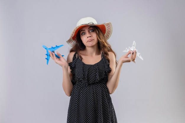 おもちゃの飛行機を保持している夏の帽子の水玉のドレスの美しい少女無知と白い背景の上に答えを持っている調達の腕でカメラ立って見て混乱
