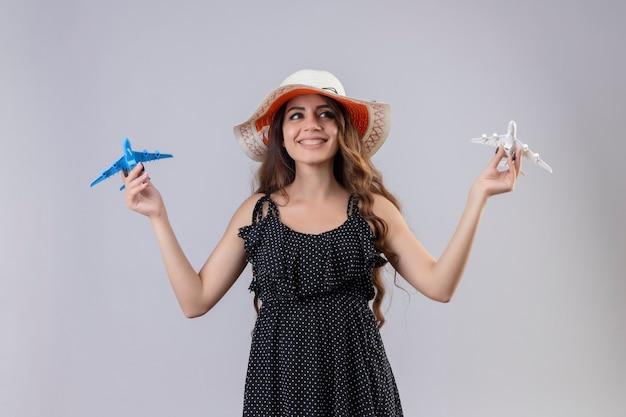 白い背景の上に元気に幸せと肯定的な立っている笑顔のおもちゃの飛行機を保持している夏帽子の水玉のドレスの美しい少女