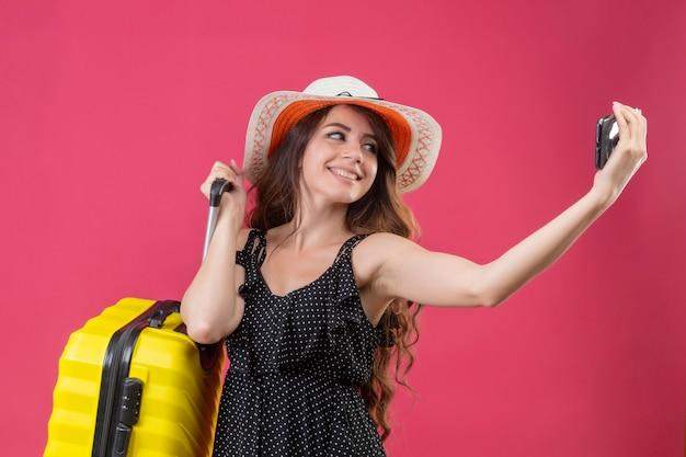 Молодая красивая девушка в платье в горошек в летней шляпе, стоя с чемоданом, глядя на экран своего мобильного телефона, весело улыбаясь, принимая селфи на розовом фоне