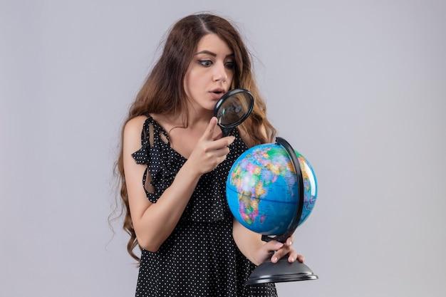 Молодая красивая девушка в платье в горошек, глядя на глобус через увеличительное стекло, заинтригована и удивлена, стоя на белом фоне