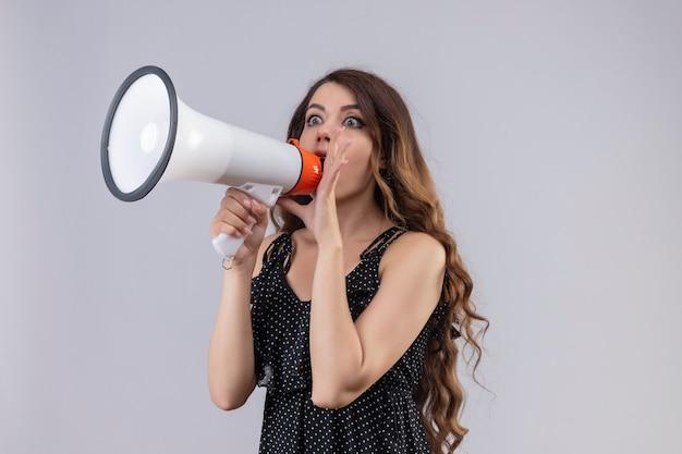 Молодая красивая девушка в платье в горошек кричит в мегафон, удивленно глядя, стоя на белом фоне
