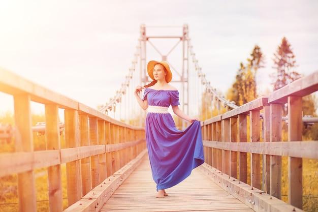 Молодая красивая девушка в платьях на природе. девушка в шляпе гуляет по парку. молодая женщина на пикнике с корзиной за городом.