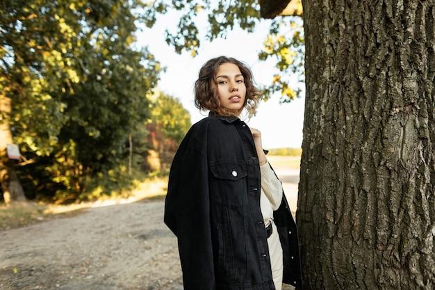 자연의 나무 근처에 서 있는 세련된 가을 옷과 청바지 재킷을 입은 젊은 아름다운 소녀