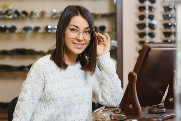 Молодая красивая девушка в очках возле стенда в оптическом магазине.