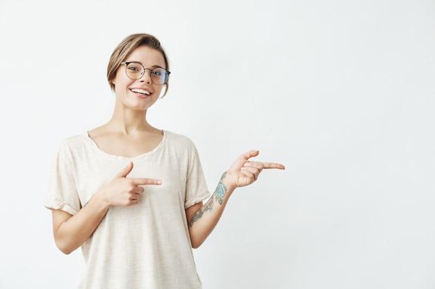 Молодая красивая девушка в очках, улыбаясь, указывая пальцем в сторону.