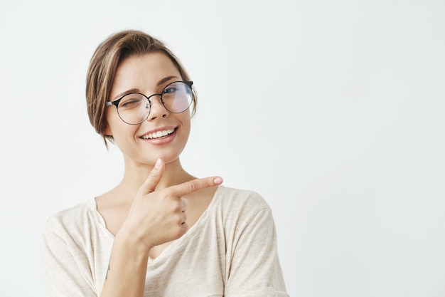 Молодая красивая девушка в очках, улыбаясь, подмигивая указательным пальцем в сторону.
