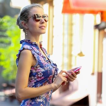 옆을 바라보는 손에 전화를 들고 안경을 쓴 아름다운 소녀