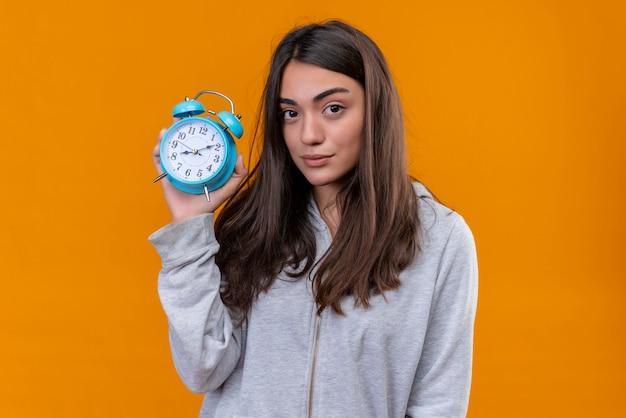 Молодая красивая девушка в серой толстовке с капюшоном держит часы и смотрит в камеру с задумчивым выражением лица, стоя на оранжевом фоне