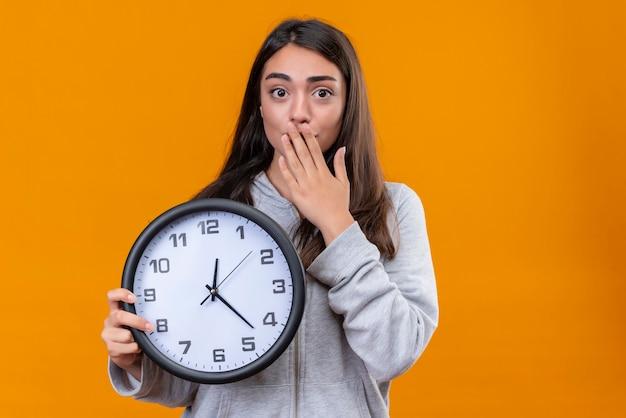Молодая красивая девушка в серой толстовке с часами держит часы и смотрит в камеру с удивлением на лице, стоя на оранжевом фоне