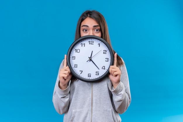 Молодая красивая девушка в серой толстовке с капюшоном держит часы и смотрит в камеру с удивленным взглядом, стоя на синем фоне