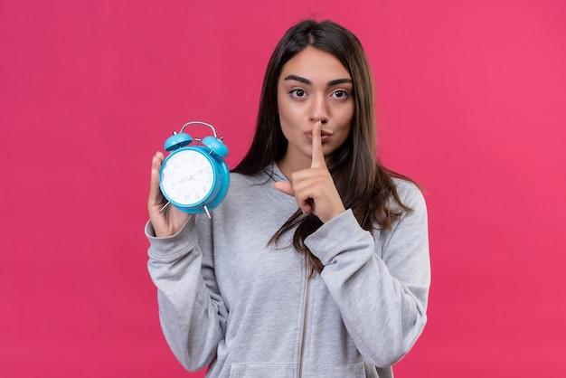 Молодая красивая девушка в серой толстовке с капюшоном держит часы, глядя в камеру с жестом молчания, стоя на розовом фоне