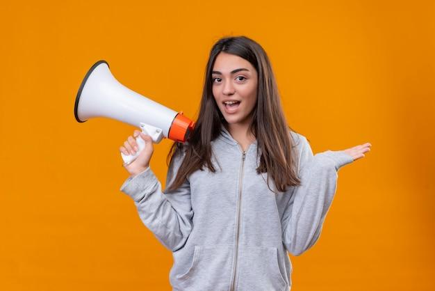 オレンジ色の背景の上に立っている驚きでカメラを見てスピーカーを保持している灰色のフーディの美しい少女