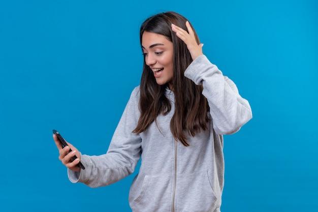 灰色の不良っぽい電話を押しながら青い背景の上に立っている顔に笑顔で電話を探している美しい少女