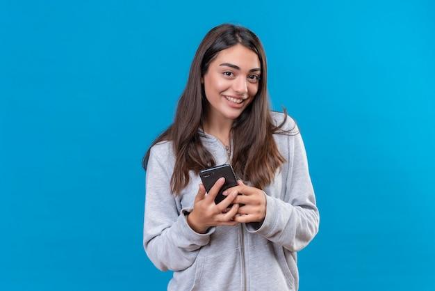 Молодая красивая девушка в серой толстовке с капюшоном держит телефон, с удовольствием смотрит в камеру, стоя на синем фоне