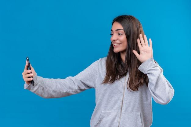 Молодая красивая девушка в серой толстовке с капюшоном держит телефон, глядя на телефон, делая приветственные жесты с улыбкой на лице, стоя на синем фоне