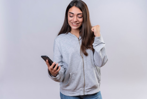 Молодая красивая девушка в серой толстовке с капюшоном держит телефон, радуясь его успеху и победе, выходит и счастлива, стоя на белом фоне