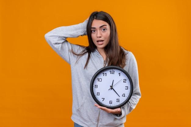 Молодая красивая девушка в серой толстовке с капюшоном смотрит на камеру, стоящую с рукой на голове за ошибку, а другую руку с часами на руке, стоящими на оранжевом фоне