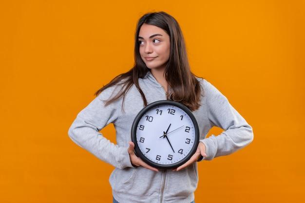 Молодая красивая девушка в серой толстовке с задумчивым взглядом смотрит в сторону и часы в руке, стоящие на оранжевом фоне