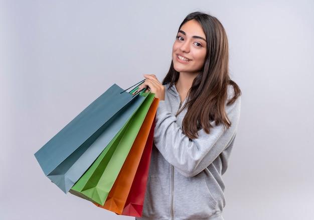 Молодая красивая девушка в серой толстовке с капюшоном смотрит в камеру с улыбкой на лице, с удовольствием держит пакеты, стоящие на белом фоне