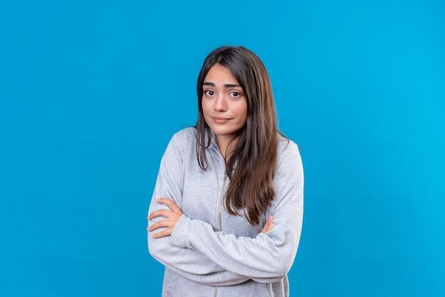 Молодая красивая девушка в серой толстовке с капюшоном смотрит в камеру со страшными эмоциями, тревожно стоит на синем фоне