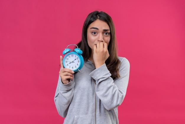 Молодая красивая девушка в серой толстовке с капюшоном смотрит в камеру с испуганным лицом, кусающим гвоздь, показывая подставку для часов на розовом фоне