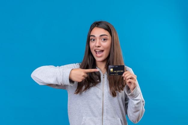 青い背景の上に立っていると指しているクレジットカードを指している顔に笑顔でカメラを見て灰色のフーディの美しい少女