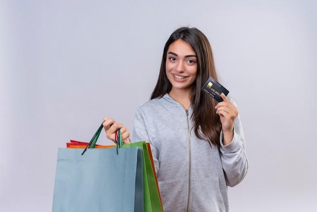 Молодая красивая девушка в серой толстовке с капюшоном смотрит в камеру с улыбкой на лице, держа пакеты и кредитную стойку на белом фоне