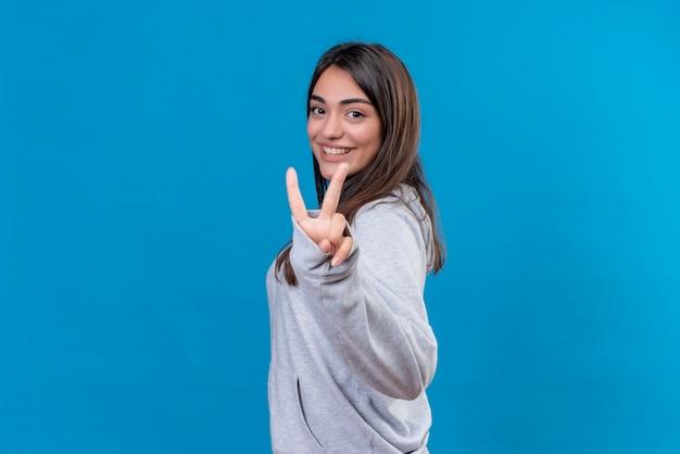 Молодая красивая девушка в серой толстовке с капюшоном смотрит в камеру с улыбкой на лице, делая жест мира, стоя на синем фоне