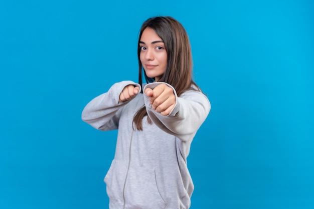 Молодая красивая девушка в серой толстовке с победными эмоциями смотрит в камеру и готова к бою, стоя на синем фоне